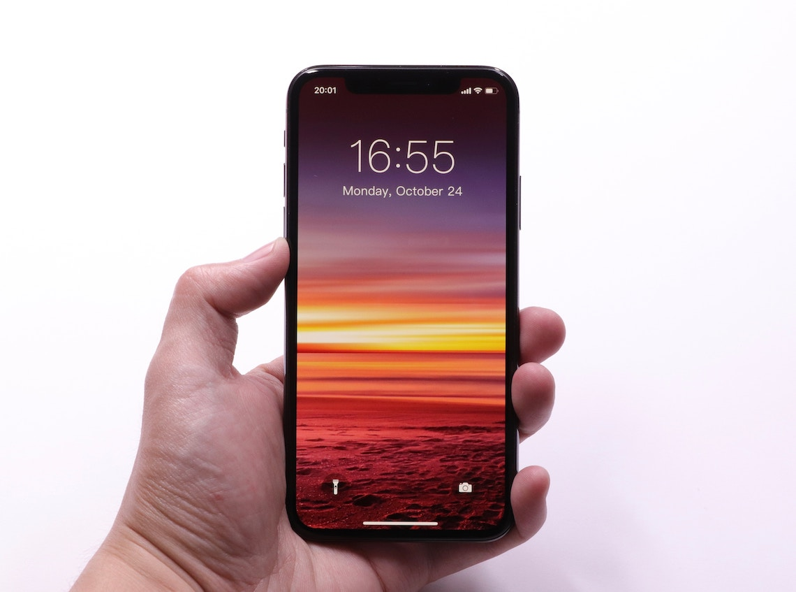 Hand holding phone with sunset image